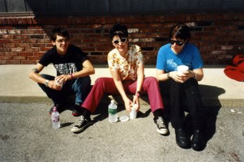 Le Tigre sit on a kerb in front of a brick wall with bottles of water.